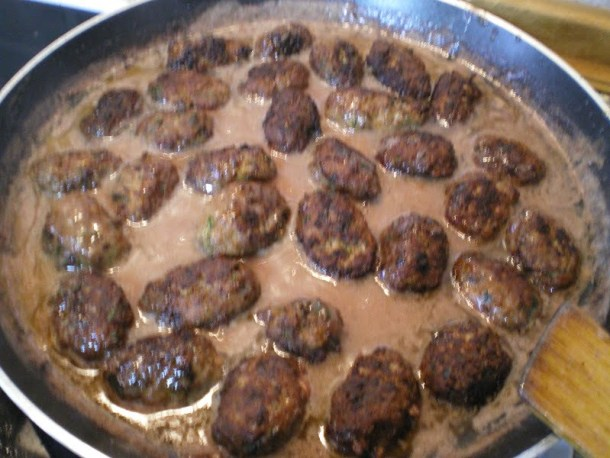 Meatballs cooking in pomegranate sauce image