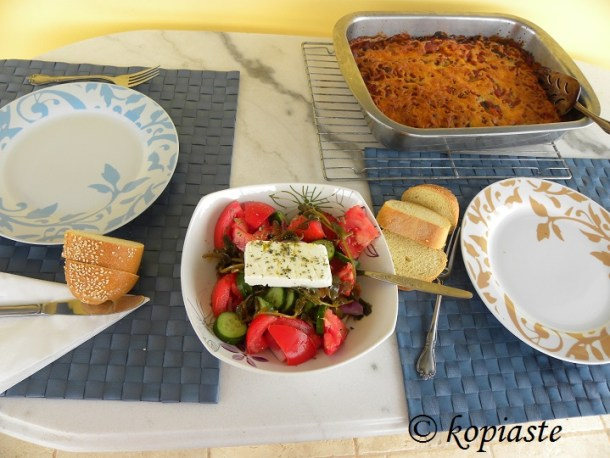 Table with Eggplant casserole and greek salad