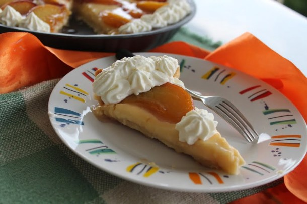 Piece of peach tarte tatin with whipped cream image