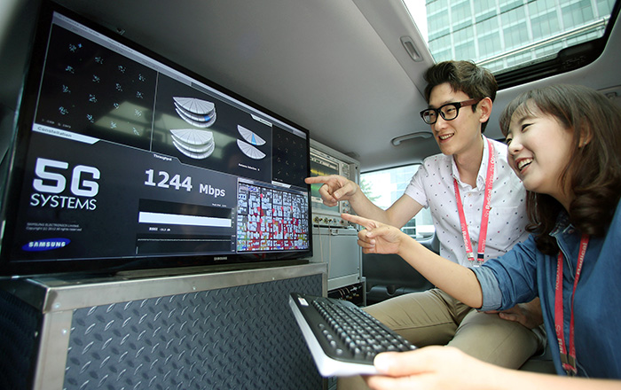 Samsung Electronics staff members smile after successfully demonstrating the company's 5G wireless system inside an express bus running at speeds higher than 100 kilometers per hour. (photo courtesy of Samsung Electronics)