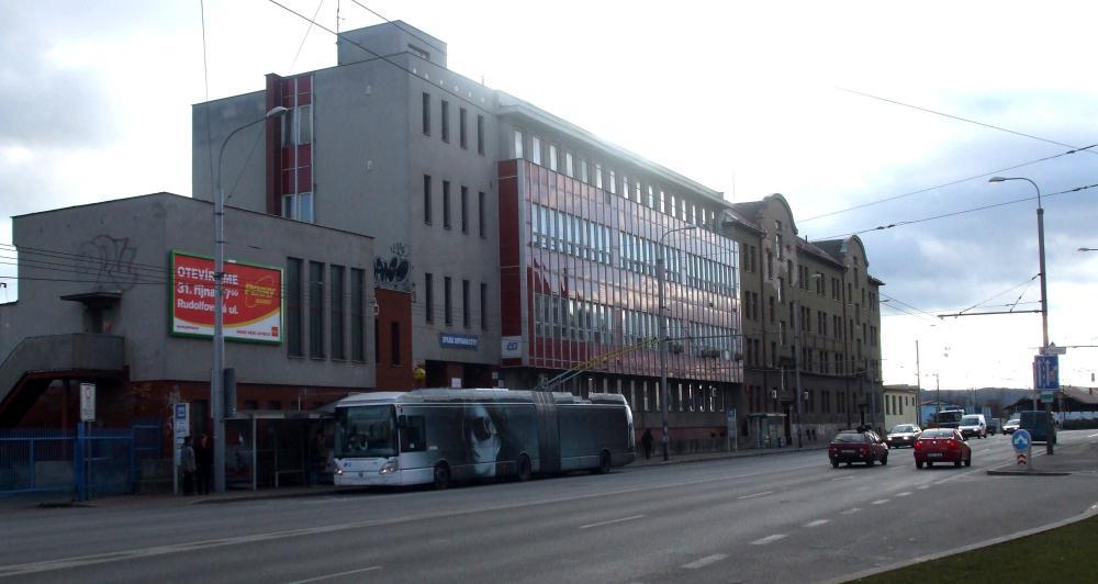 Pohled na stejné místo dnes. Železniční poliklinika a kanceláře v Nádražní ulici. Budova vzadu vystavěná v roce 1912 sloužila kdysi jako nocležna pro strojní a vlakové mužstvo.