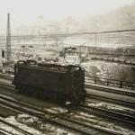 Osobní nádraží v Praze-Vršovicích v roce 1947. Za elektrickou lokomotivou ř. E 467.0 je patrná nejen polní drážka, ale zejména rozšířená nádražní pláň nasypaným materiálem z ražby dvou nových vinohradských tunelů.