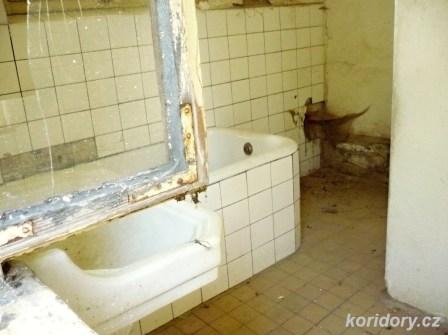 Chotoviny - ač jsou vchodové dveře domku zamčené, rozbitými okny lze nahlédnout dovnitř domku, třeba do koupelny.