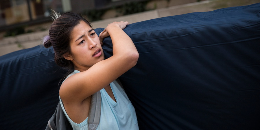 NEW YORK, NY - SEPTEMBER 05: Emma Sulkowicz, a senior visual arts student at Columbia University, carries a mattress in protest of the university's lack of action after she reported being raped during her sophomore year on September 5, 2014 in New York City. Sulkowicz has said she is committed to carrying the mattress everywhere she goes until the university expels the rapist or he leaves. The protest is also doubling as her senior thesis project. (Photo by Andrew Burton/Getty Images)