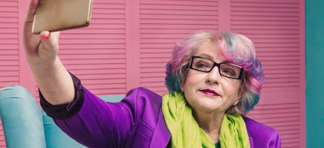 senior woman with rainbow hair holding gold smart phone