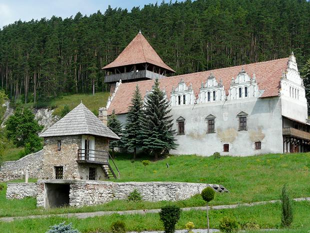 A kastely partazatos falaival, nyugati oldalan ketszintes kapuepuletevel a Lazrok gyergyoszarhegyi kastelyaval vetheto ossze