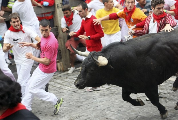 Runners lead a Torrestrella ranch bull during the first bull run of the San Fermin Festival in Pamplona July 7, 2011.  REUTERS/Joseba Etxaburu (SPAIN - Tags: ANIMALS SOCIETY)