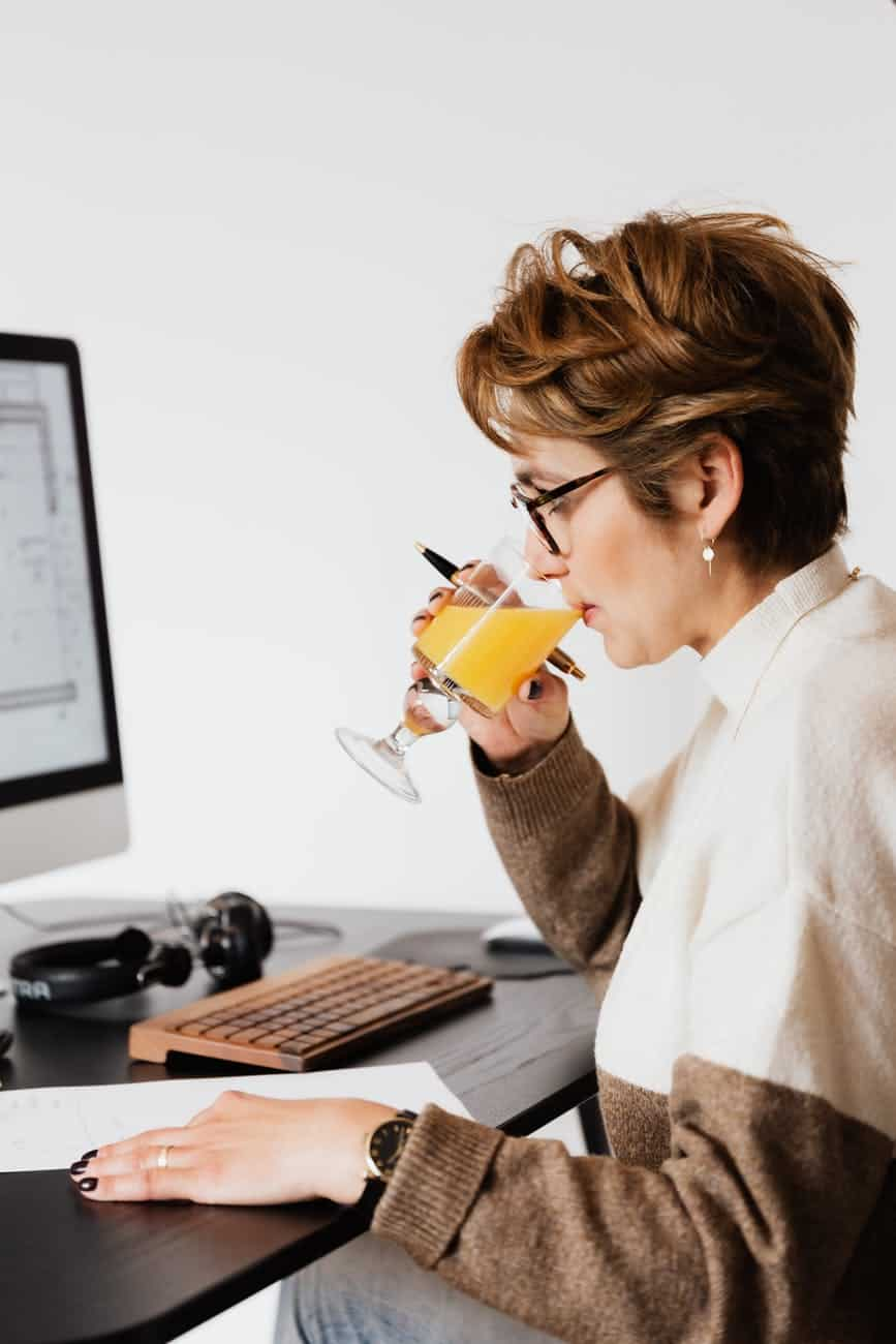 focused female drinking refreshing juice while working at table in office