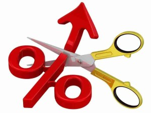 Ein rotes nach oben gerichtetes Prozentsymbol wird mit einer Schere zerschnitten. Durch die Einschaltung von Kreditvermittlern Darlehenszinsen sparen.