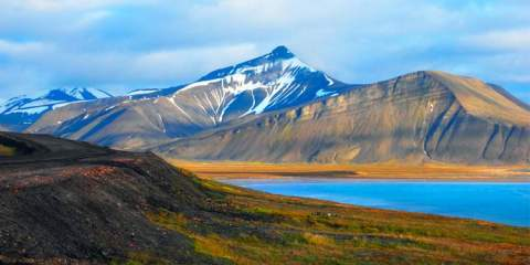 Beautiful scenic view of Blue Gulf under Barren mountain range, with melting snow against the background of a dramatic evening sky, near Baren tsburg, Spitsbergen (Svalbard Island), Norway, Greenland sea.