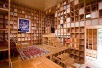 Photo of a crazy bookshelf house. No walls, just shelves.