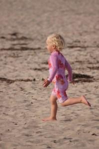 Little girl joyously running across the beach