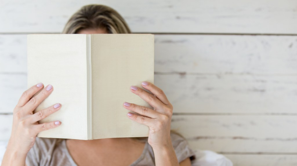 Woman reading a book and covering her face