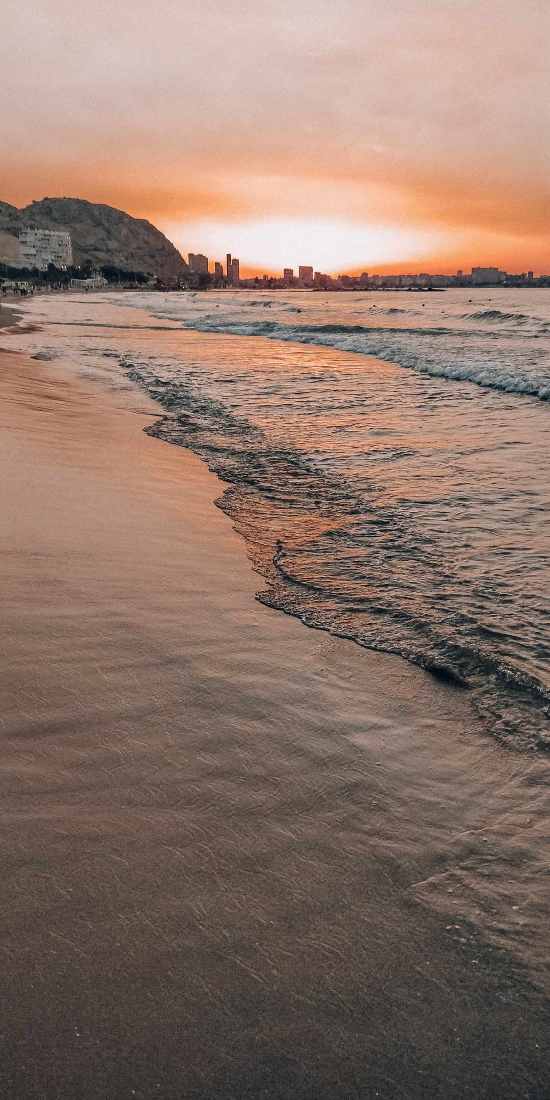 Pink sunrise in Alicante beach with waves