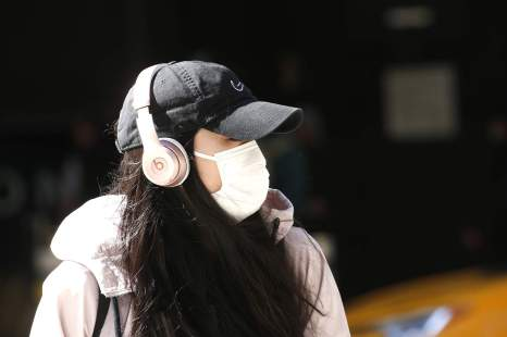 NEW YORK, NY - MARCH 27:  A woman wearing a mask and headphones is seen near 7th Avenue as New York City attempts to slow down the spread of coronavirus through social distancing on March 27, 2020.  New York has been hit hard by the restrictions in response to the outbreak of COVID-19. (Photo by John Lamparski/Getty Images)