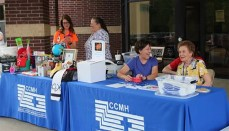 CCMH staff and Auxiliary volunteers stationed at the check-in table of the Health Fair & Family Fun Night.
