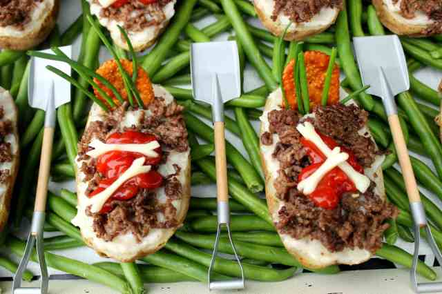 Twice Baked Potato Graves with ground beef dirt, mushroom soup, a cracker tombstone, chive grasses and string cheese bones.