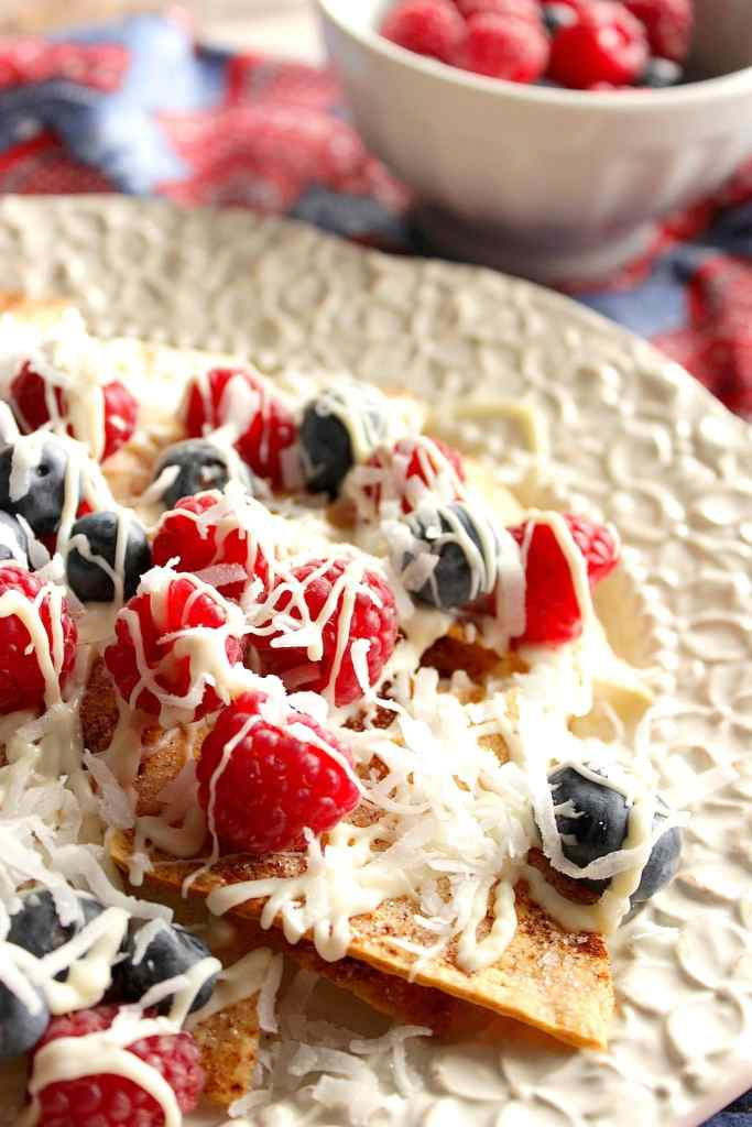 Red, White, & Blue Dessert Nachos are a patriotic sweet treat your family and friends will devour. Homemade cinnamon sugar tortilla chips are generously toppedwith red and blue seasonal berries along with a white chocolate drizzle and sweetened coconut. - kudoskitchenbyrenee.com