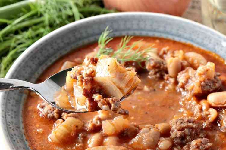 Closeup shot of White Bean, Fennel & Italian Sausage Soup on a spoon. - www.kudoskitchenbyrenee.com