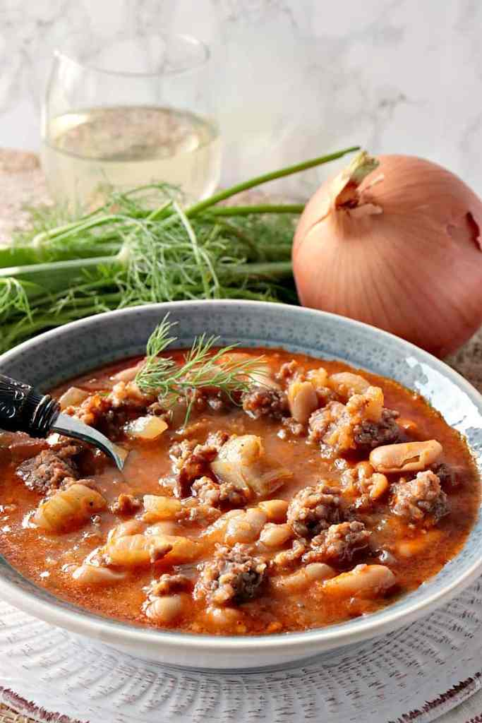A hearty bowl of White Bean, Fennel & Italian Sausage Soup with Fennel, Onion and a glass of wine.
