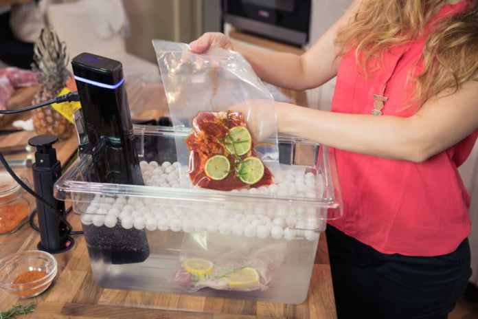 Sous-vide sticks are hung on the edge of a heat-resistant pot, where they are usually attached with a clamp. The cooking time and temperature can be set on the display. (Photo: Adobe Stock / FotoCuisinette)