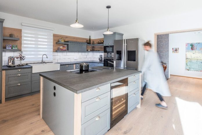 Consistent design line: the oak wood of the floorboards can also be found in the cheeks of the kitchen furniture and as wall cladding.  This creates the impression of a custom-made unique item.  (Photo: WohnHaus Grill & Ronacher)