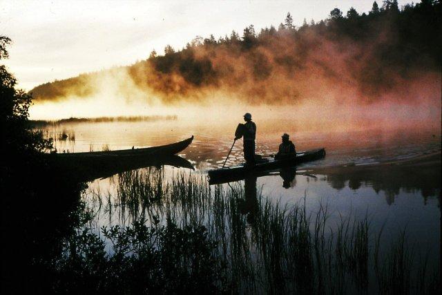 Martti Helenius ja Pentti Kähkönen melovat aamusumusta Korsajärven rantaan Kultamuseon veneen viereen. Koko muu joukko eksyi Naskamajoelle ja oli täällä aamutunneilla koko yön soutamisen ja sauvomisen jälkeen. Vietettiin yksi ylimääräinen lepopäivä.