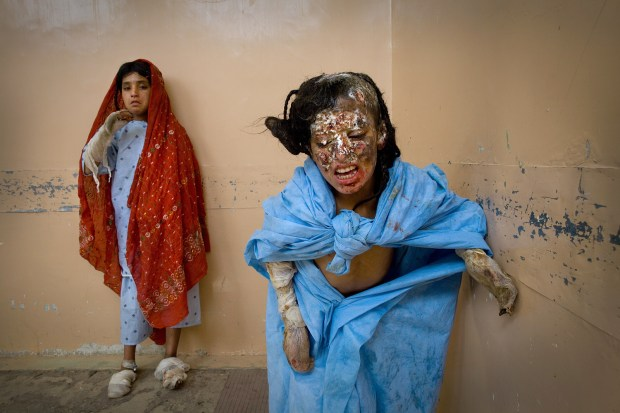 KANDAHAR, AFGHANISTAN - OCTOBER 13: (EDITORS NOTE: Image contains graphic content.) Asan Bibi, 9, (R) and her sister Salima,13, (L) stand in the hallway of Mirwais hospital October 13, 2009 Kandahar, Afghanistan. Both were burned when a helicopter fired into their tent in the middle of the night on October 3rd, according to their father. Three members of the family were killed in the incident. The family belongs to the Kuchi ethnic tribe, nomads living in tents out in the open desert whom are very vulnerable to a war they have little understanding of. Mirwais hospital in Kandahar city is the largest regional hospital in the area, supported by the ICRC and the Afghan government it caters to most of the war wounded in the most hostile part of the country. A recent U.N. report has described 2009 as the deadliest year in terms of civilian casualties in Afghanistan ever since the start of the U.S.-led war against Taliban in the country. In his latest report presented to the Pentagon, Gen. Stanley McChrystal, the U.S. top commander emphasized the need for winning the hearts and minds of the Afghans. The Taliban are now staging suicide attacks and IED blasts in densely populated areas to create a bigger impact as more of Afghan's war wounded hit the headlines. (Photo by Paula Bronstein/Getty Images)