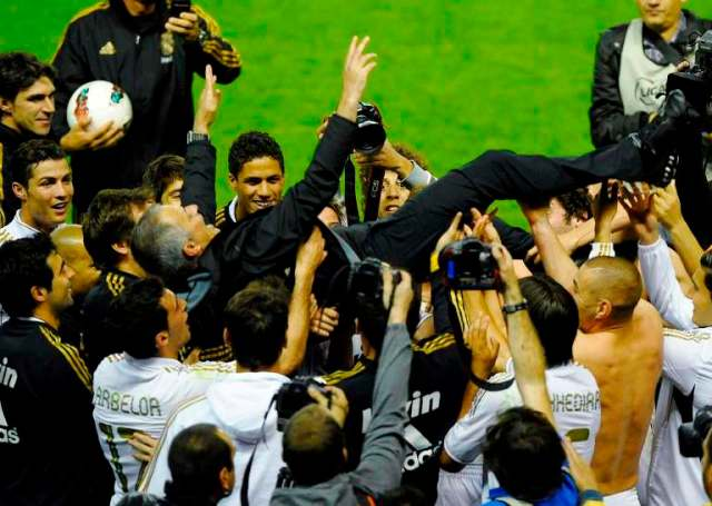Real Madrid's coach Jose Mourinho is thrown in the air by his players after their win over Athletic Bilbao to win the Spanish first division league title at San Mames stadium in Bilbao May 2, 2012. REUTERS/Vincent West (SPAIN - Tags: SPORT SOCCER)