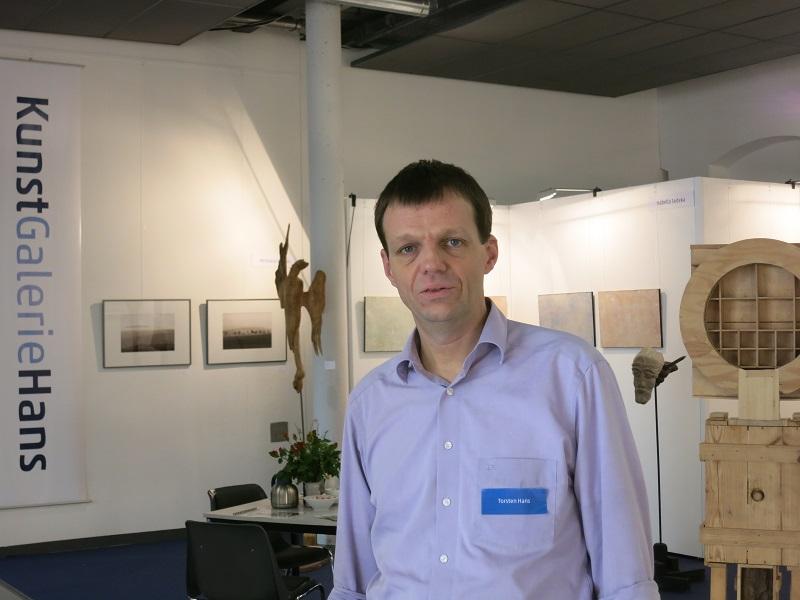 Inhaber Torsten Hans vor Messestand auf Kunstmesse Neue Art 16