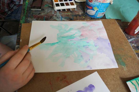 Hand mit Pinsel über einer Aquarellmalerei, Farbkasten