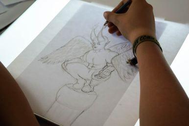 Hand eines Teilnehmers, der am Leuchttisch eine Skizze anfertigt: geflügelter Charakter mit Hörnern.