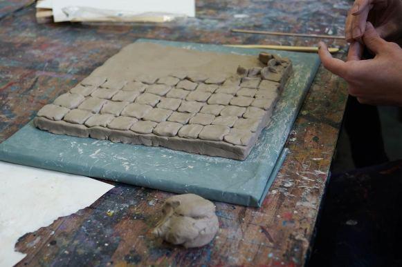 Kleine Quadrate aus Ton, die auf einem großen Quadrat aus Ton angeordnet werden, Arbeit im Prozess.