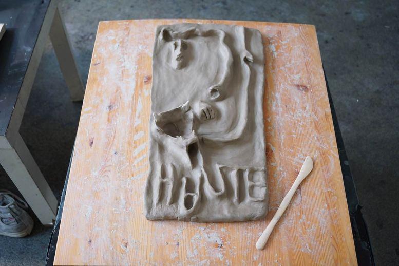 Buchstaben und Elemente von Gesicht und Hand auf einem Tonrelief.
