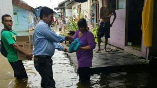 Anggota DPRD Kota Samarinda, Joni Ginting, menyerahkan bantuan kepada korban banjir di Samarinda, Kamis 13/6/2019 (dok. KM)