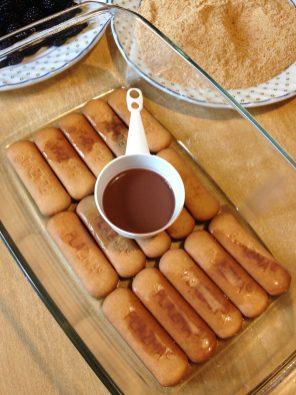 3. U dublju vatrostalnu posudu, ili kalup poređati jedan red keksa i preliti sa hladnim čokoladnim mlekom.