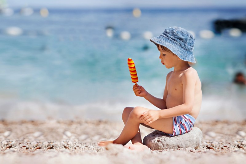 boy eating popsicle on the beach