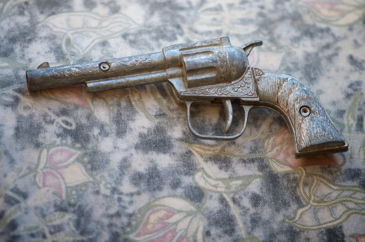 Antique toy gun sits on an old weathered fabric background