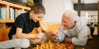Close up of a grandfather and grandson playing chess