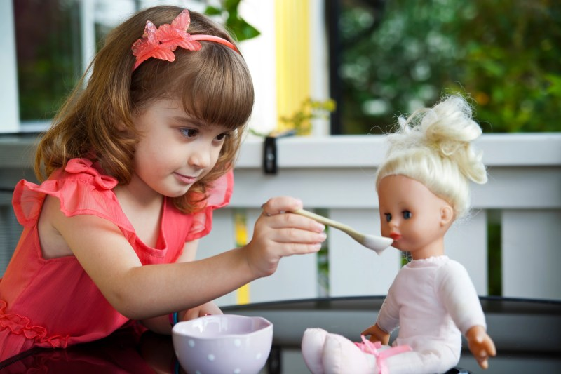 Little girl feeding a doll with a spoon.