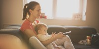 Young woman sitting on the bed holding baby and remote controler