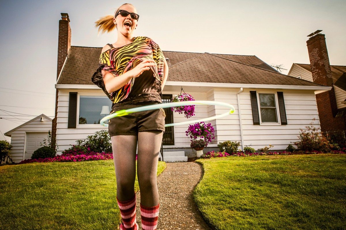 A 1980's styled young woman with leg warmers, off-shoulder shirt, side ponytail and sunglasses hula hoops on the sidewalk in front of her home in the suburbs, a bright blue sky overhead. She smiles and laughs with a happy look on her face; she's jumping mid-air. Horizontal with copy space.