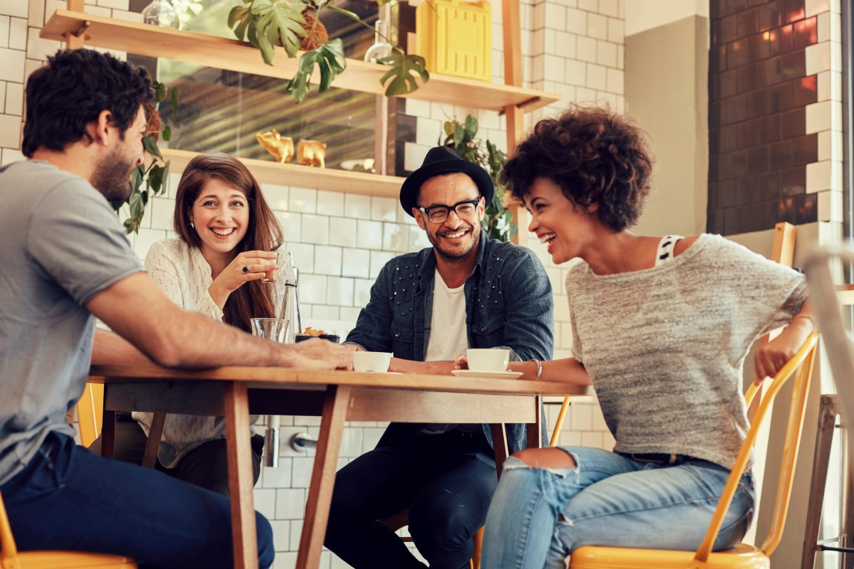 Portrait of cheerful young friends having fun while talking in a cafe. Group of young people meeting in a cafe.