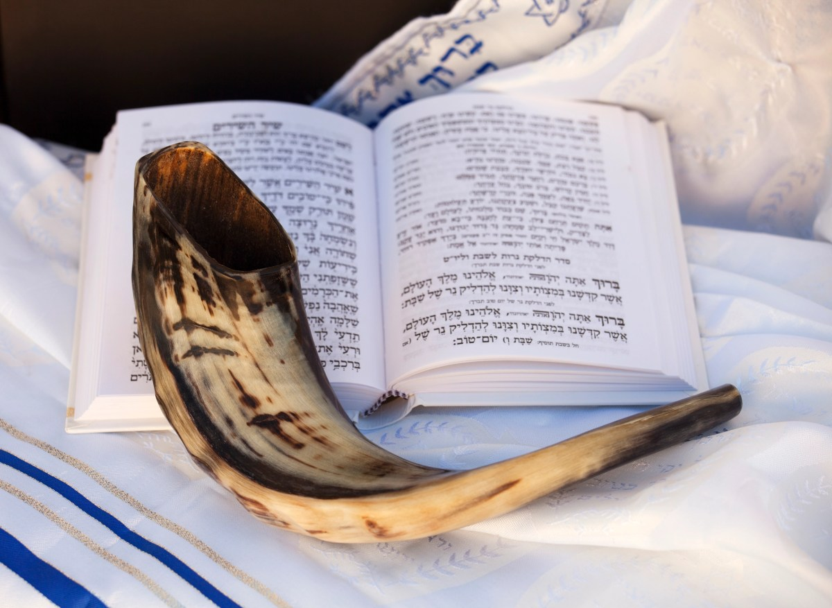 Shofar and Hebrew prayer book on a Talit (prayer Shawl)