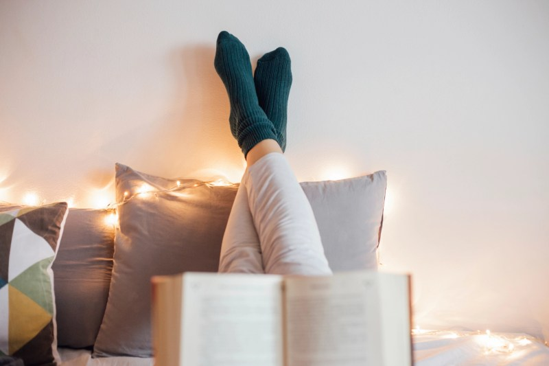 Young women relaxing in bad while reading book and enjoying in decorative light