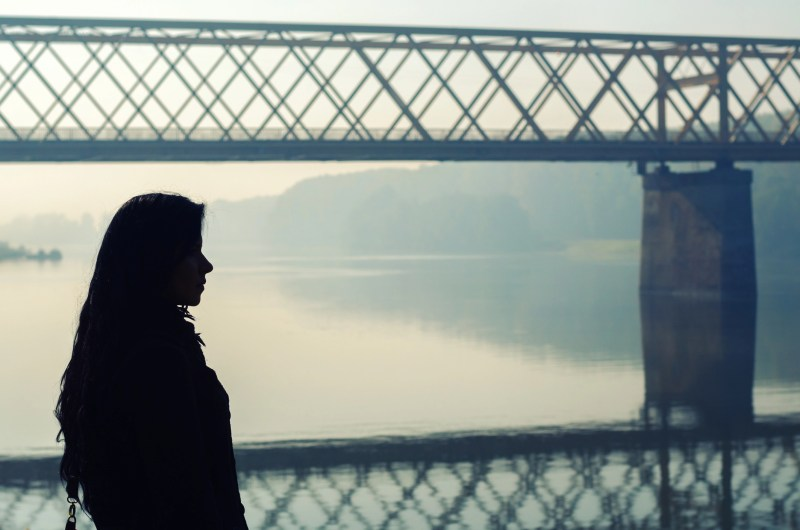 Silhouette of beautiful girl standing on dock with bridge in background on sunny autumn day.