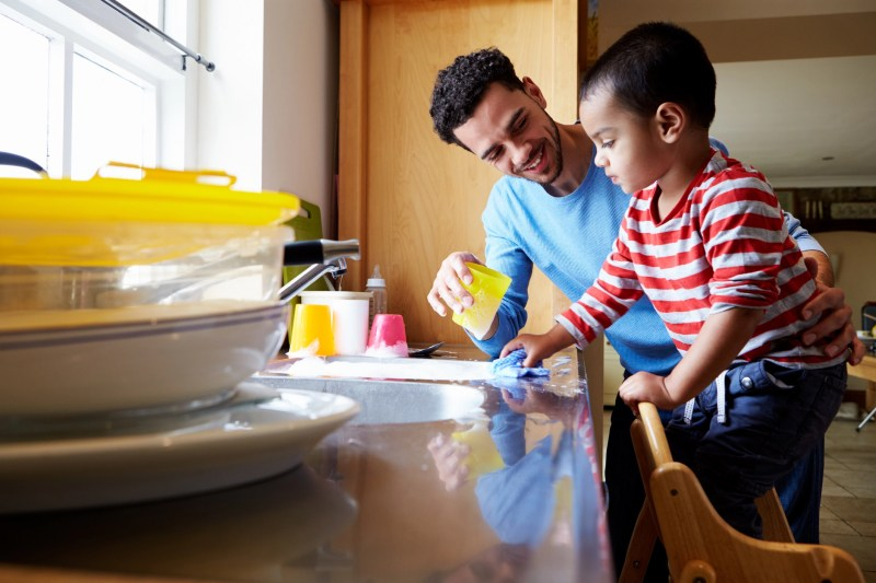 Son Helping Father To Wash Dishes In Kitchen Sink