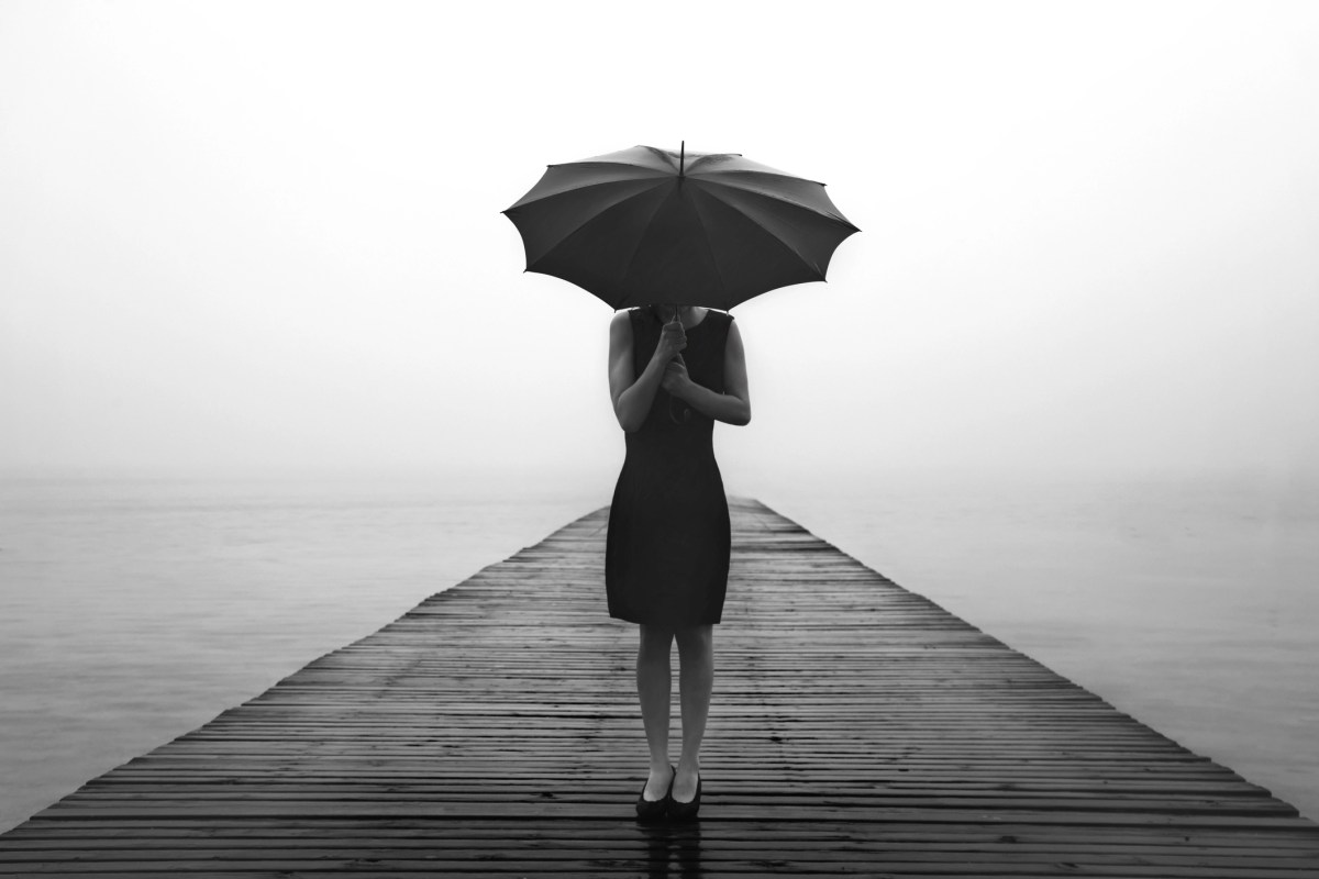 woman with umbrella contemplates peacefully in front of a mysterious lake
