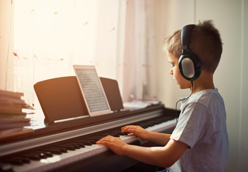 Little boy practicing playing digital piano near window on a sunny day. The boy is using headphones and tablet is displaying the musical notes.
