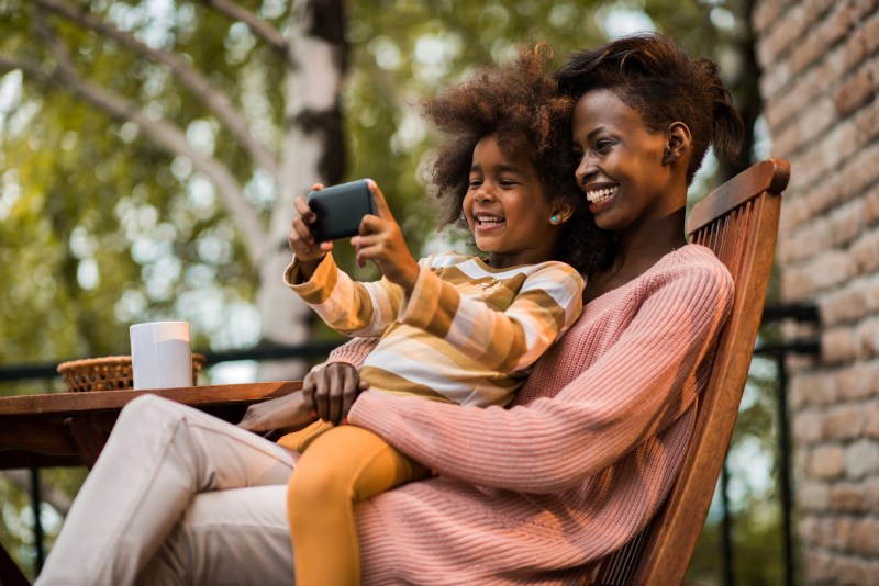 Smiling African American mother and daughter relaxing on a terrace and taking a selfie with cell phone.